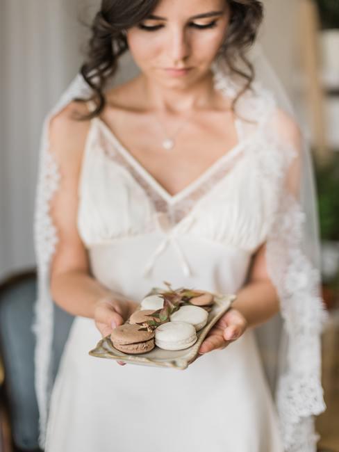 Een vrouw in een trouwjurk met een cadeau voor gasten in haar hand