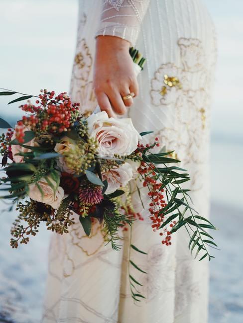 Een vrouw in een trouwjurk met een bruidsboeket bloemen in haar hand