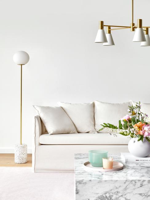 Bekleding reinigen: close-up op witte zitbank naast een vloerlamp en salontafel met vaas