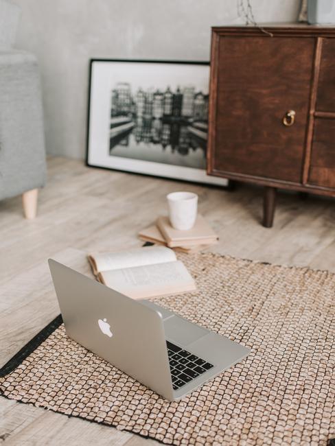 Laptop op het vloerkleed en naast het houten dressoir en ingelijste print