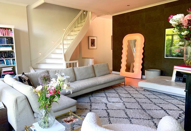 Woonkamer Noor de Groot met lounge zitbank op wit geruit vloerkleed en witte trap