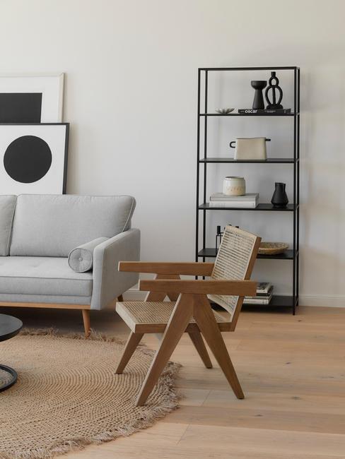 Feng shui woonkamer met rotan stoel en grijze zitbank naast zwarte wandrek
