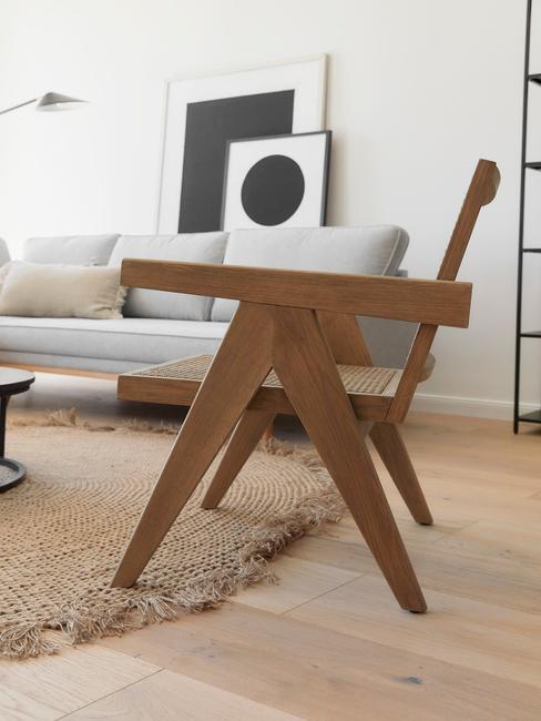 Retro woonstijl rotan stoel met grijze bank en zwart witte schilderijen