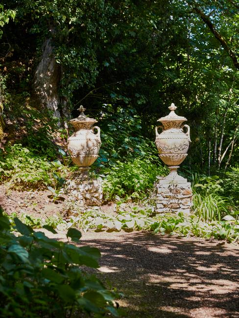 Feng shui tuin met twee standbeelden van potten in wilde tuin