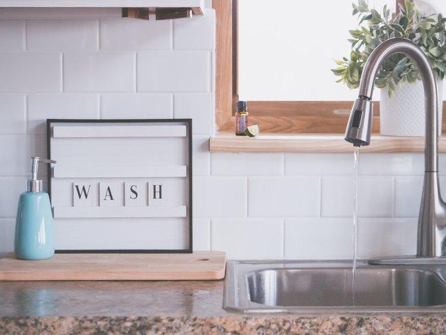 Keuken gootsteen in metaal e hout en raam, vloeibare zeep en letterbord met wash erop