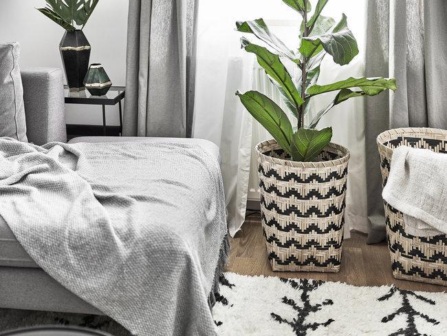 Bed met grijze bedsprei, groene plant in rieten mand met zwart patroon en grijze en witte gordijnen voor raam