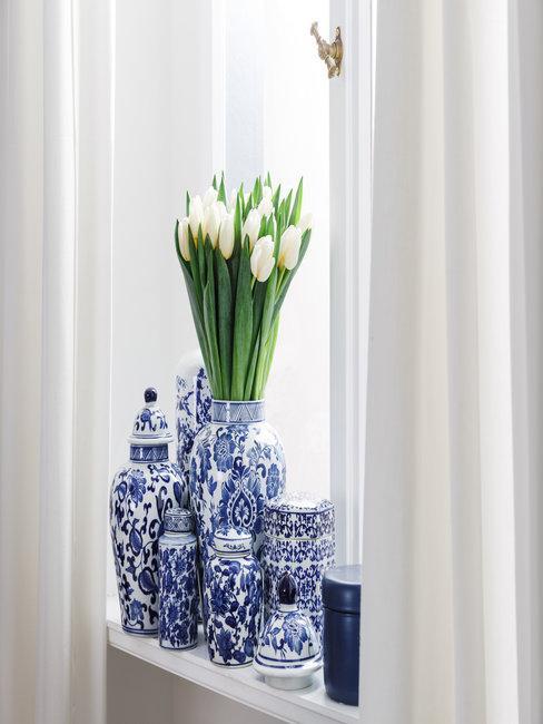 blauwe ming vazen met witte tulpen voor een raam met witte gordijnen errond : gordijnen wassen