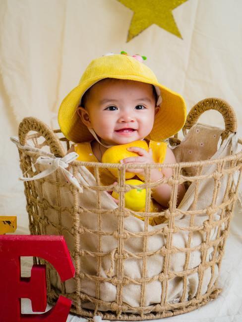 baby in geel hoedje in rotan mandje