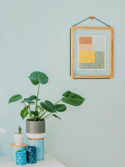 Babykamer groen: groene muur met ingelisjte print en plantenpot op sideboard