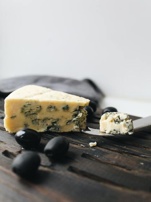 Blauwe kaas op een houten bord naast olijven