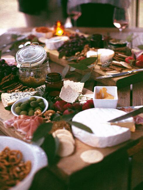 Een bord met kaas, vleeswaren en fruit op een houten tafel