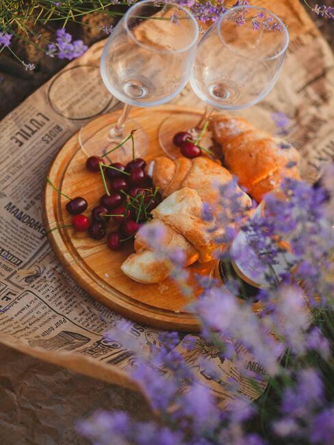 Kaasplankje met kersen op tafel met een vaas met bloemen en wijnglazen