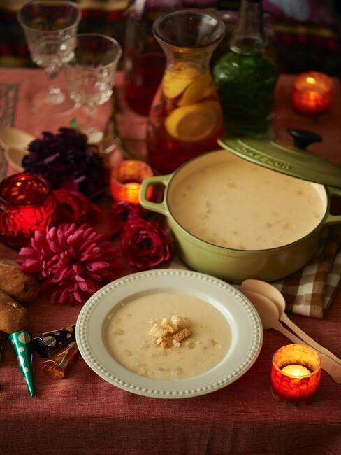 Voorgerechten kerst: soep in een kom en pot geserveerd op een houten tafel