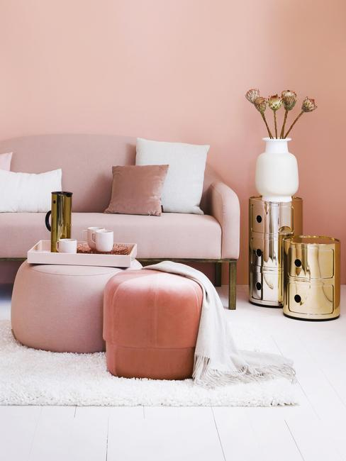 Fluwelen zitbank in roze met roze en witte sierkussens naast fluwelen kruk