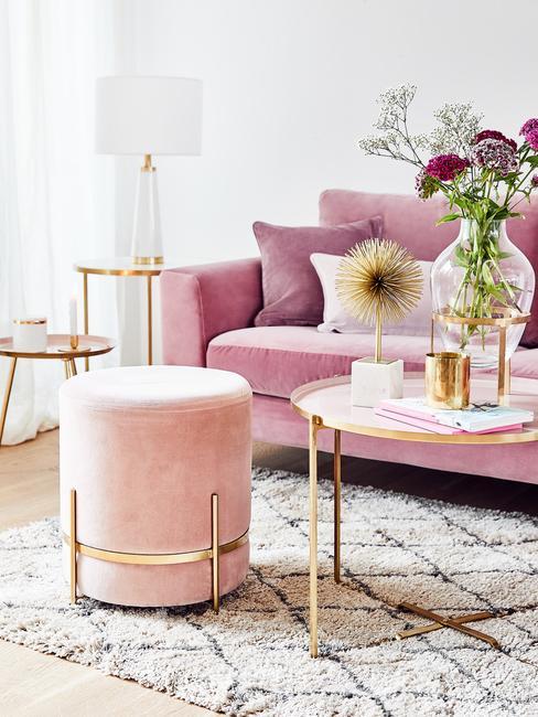 Velvet: roze zitbank met sierkussens en kruk naast een goudkleurige salontafel