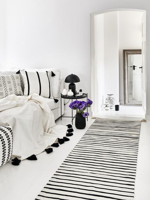 Biała sypialnia z czarno-białym dywanem oraz narzuta i poduszkami na łóżku