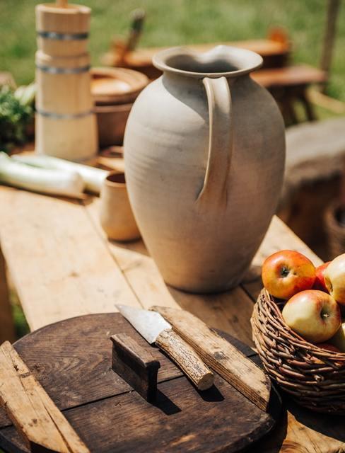 Stół stojące na dworze z ceramicznym dzbankiem oraz koszykiem z jabłkami