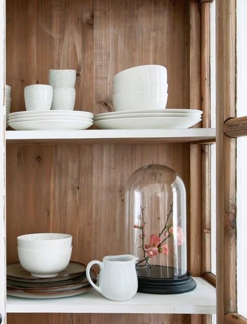 Drewniana szafa z biłymi, ceramicznymi i roślinną dekoracją w szkle