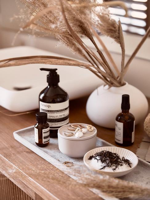 Półka w łazience z kosmetykami w czarnych buteleczkach, w wazonie trawy ozdobna
