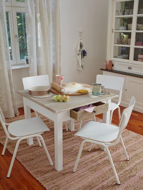 Fragment jadalni z białym stołem, czterema krzesłami oraz dywanem