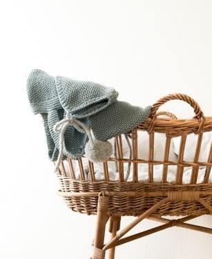 Pleciony kosz dla niemowlaka z białą pościelą oraz niebieskim swetrem