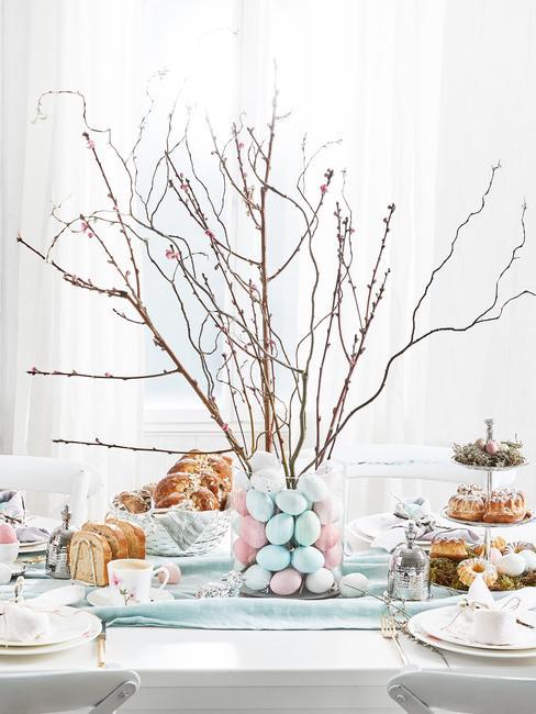 Stojący stroik wielkanocny stworzony z gałązek oraz pastelowych pisanek ustawiny na zastawionym stole wielkanocnym