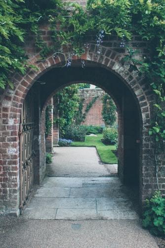 Ceglany łuk wejściowy do ogrodu angielskiego