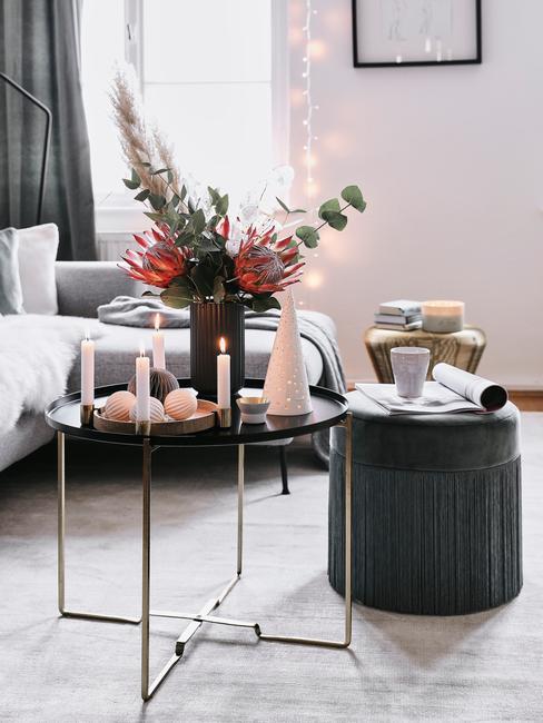 Bukiet kwiatów oraz gałęzek eukaliptusa w czarnym wazonie na stoliku w udekorowanym świątecznie wazonie