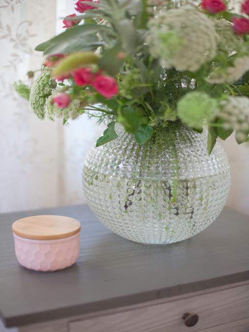Bukiet różnych kwiatów w szklanym wazonie na drewnianym stoliku