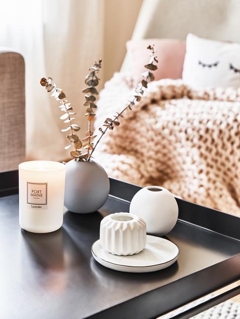 Czarny stolik stojące przez sofą z kocem, na tkórym znajduje się świeczka oraz dwa wazony