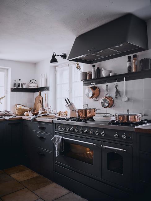 Kuchnia z czanrymi szafkami, kuchenką i okaptem oraz z białymi kafelkami na ścianie