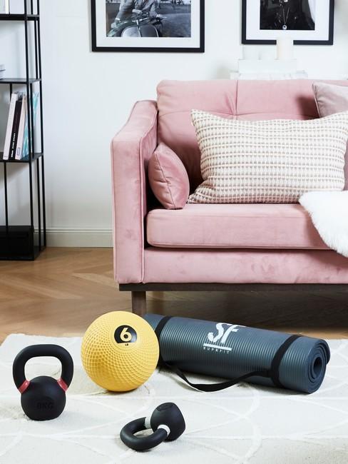 Fragment salonu, w którym urządzono kącik do ćwiczeń z różową sofą oraz białym dywanem