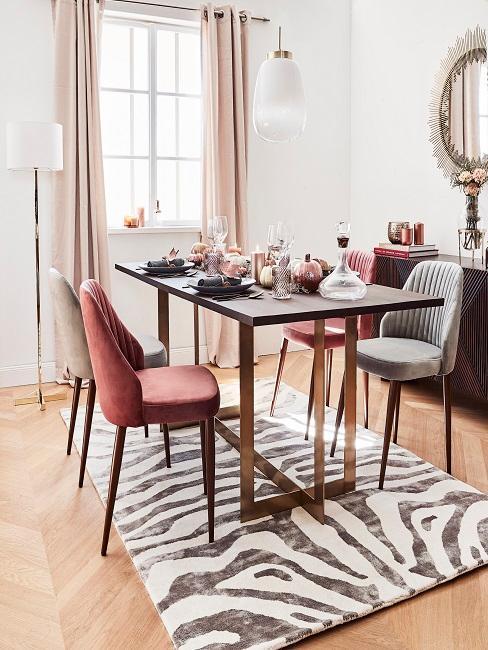 Jasna jadalnia z czarnym stołem, krzesłami w różnych kolorach oraz dywannem ze wzorem z zebre