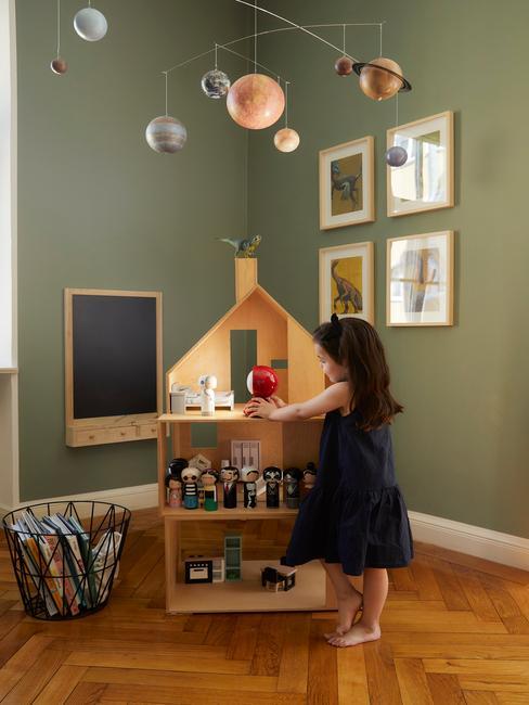 Pokój dziecka z zielonymi ścianami, obrazkai, tablica, domkiem dla lalek i dekoracją doczepioną w lampy