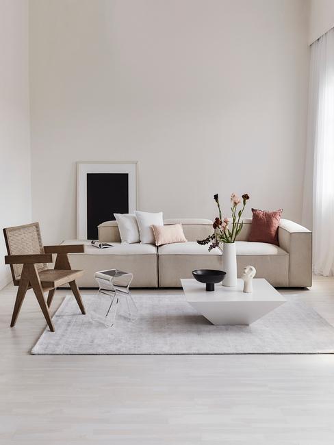 Jasny, minimalistyczny salon z beżową sodą, białym stolikiem oraz rattanowym krzesłem