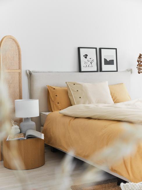 Biała sypialnia w stylu boho z pomarańczową pościlą