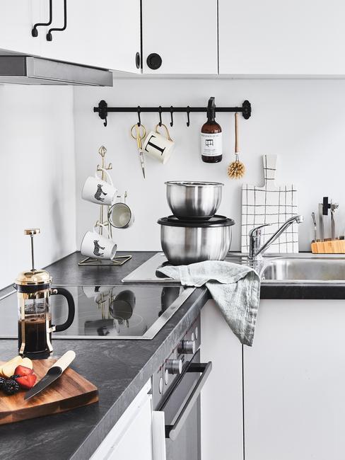 Zorganizowana biała kuchnia z relingiem, kawiarką, miskami oraz deską do krojenia