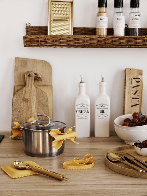 Zbliżenie na drewniany blat z deskami, garnkiem oraz pojemnikami na oliwę oraz wiklinową półką