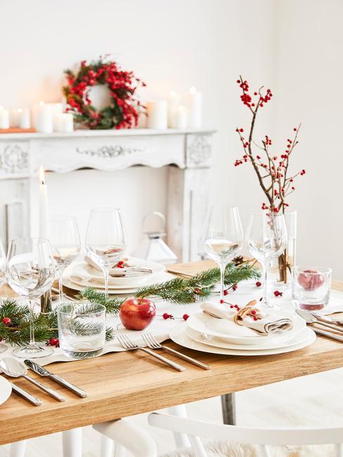 Drewniany stół udekorowany gałązkami świerku, wazonem z gałązką, białą zastawą oraz sztućcami w salonie