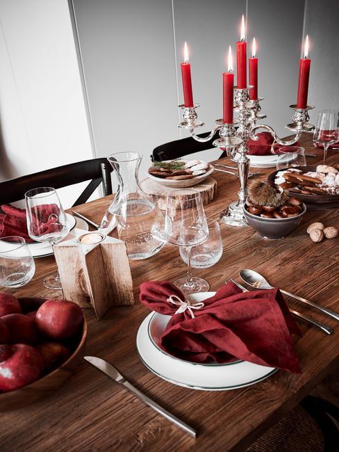 Drewniany stół zastawiony na kolację wigilijną, gdzie dominującym kolorem jest czerwony