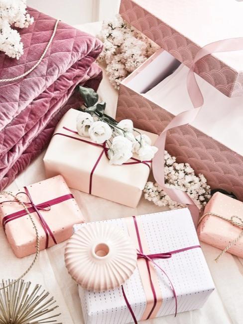 Regalos envueltos en papel rosa, vainilla y jarrón con flores