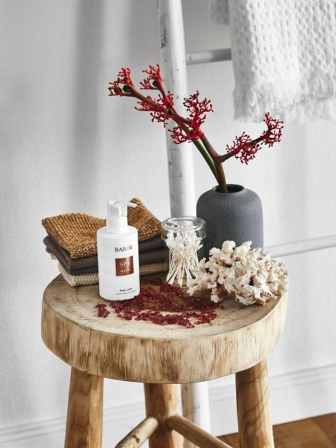 Decoración de cuarto de baño de invitados con taburete de madera y jarrones con flores