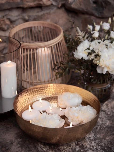Goldene Schale mit weißen Kerzen und Windlicht als Kerzendeko