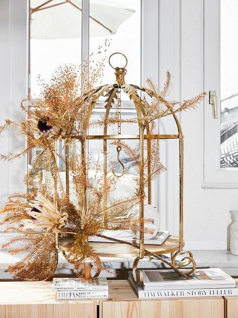 Vogelkooi met decoraties op de vensterbank, waaronder gouden bloemen.