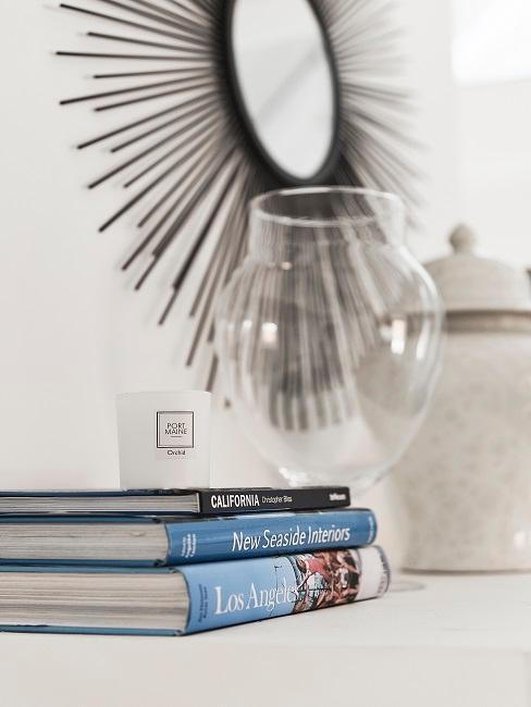 Szklany wazon w jasnym pomieszczeniu a przed nim książki