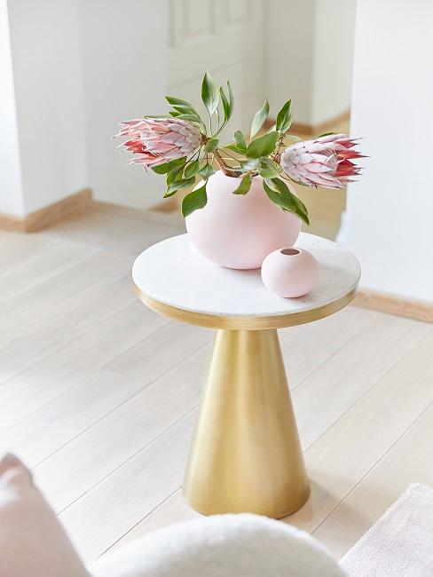 Dwa jasnoróżowe wazony z egzotycznymi kwiatami.