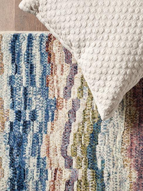 alfombra de colores azul y beige, un cojín beige
