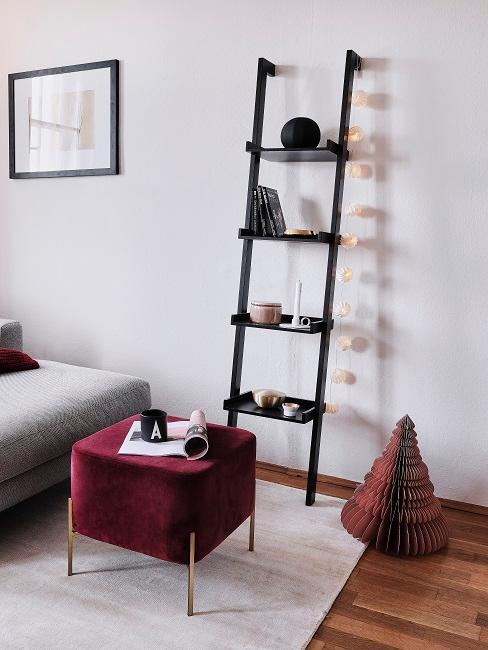 Leiterregal an der Wand, davor ein Hocker in Bordeaux aus Samt