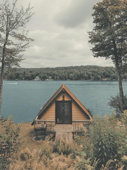 Ein Tiny House steht auf einem Grundstück am See umgeben von Gräsern und Bäumen.
