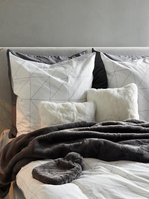 Ein Bett im Schlafzimmer mit geometrischer Bettwäsche.
